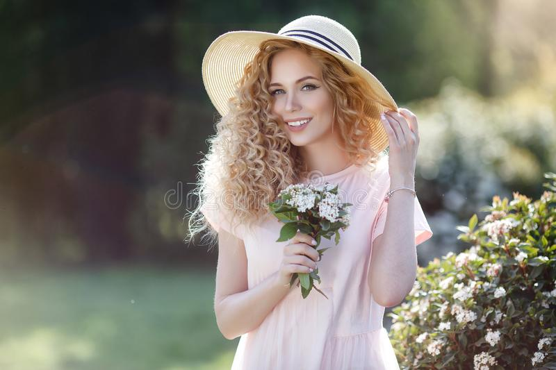 Attractive young woman in a straw hat alone in a blooming spring park stock image