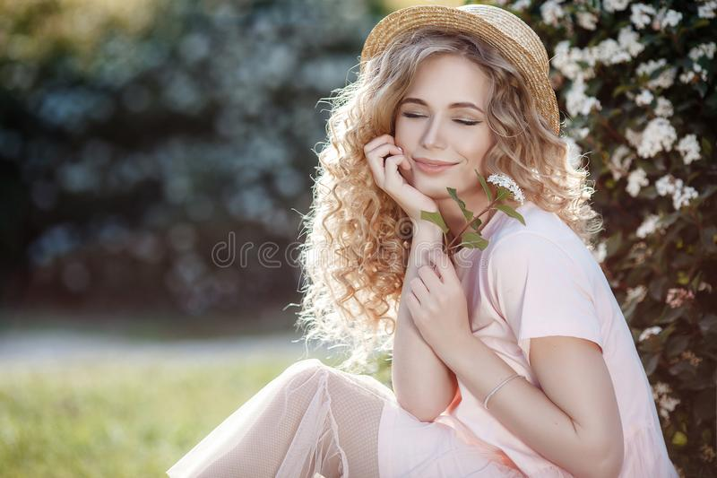 Attractive young woman in a straw hat alone in a blooming spring park royalty free stock photo