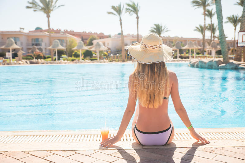 Attractive young woman in straw hat and bikini enjoy in sunny summer day with cocktail royalty free stock photo