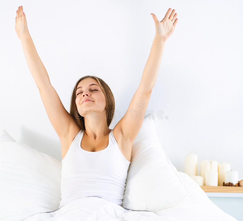 Attractive young woman stretching in bed after waking up. An attractive young woman stretching in bed after waking up royalty free stock images