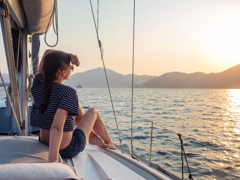 Attractive young woman in a striped t-shirt enjoys the sunset on the deck of a sailing yacht. Girl yachtsman. Looks into the distance. Sailing regatta, sea royalty free stock photo