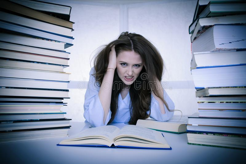 Attractive young woman student undre stress while studiing for e royalty free stock photos