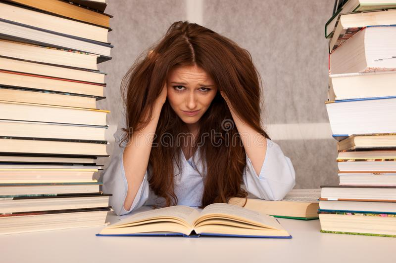 Attractive young woman student undre stress while studiing for e royalty free stock photography
