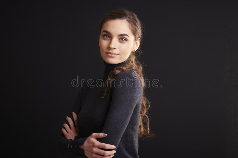 Attractive young woman studio portrait while standing at dark background royalty free stock photos