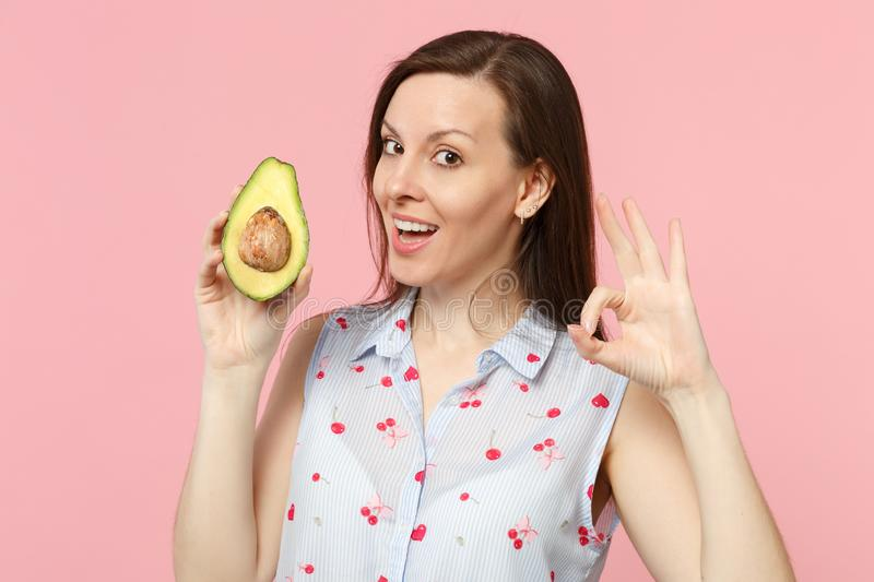 Attractive young woman in summer clothes showing OK gesture, hold fresh ripe green avocado fruit isolated on pink pastel royalty free stock photography