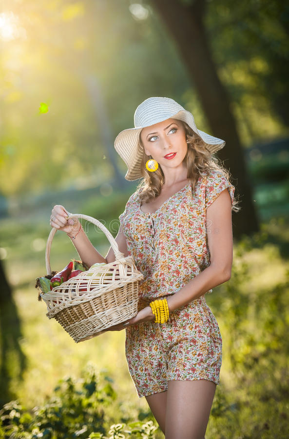 Attractive young woman in a summer fashion shot. Beautiful fashionable young girl with straw basket and hat in park near a tree royalty free stock photography