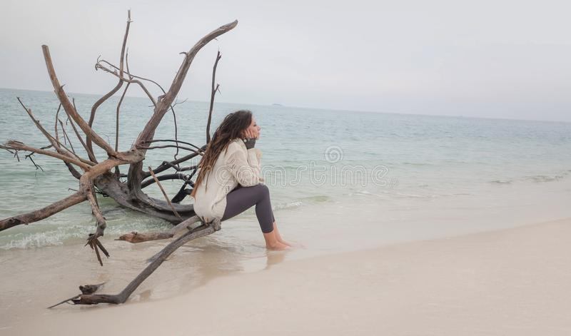 Attractive young woman in sweater sitting on beach. royalty free stock photos