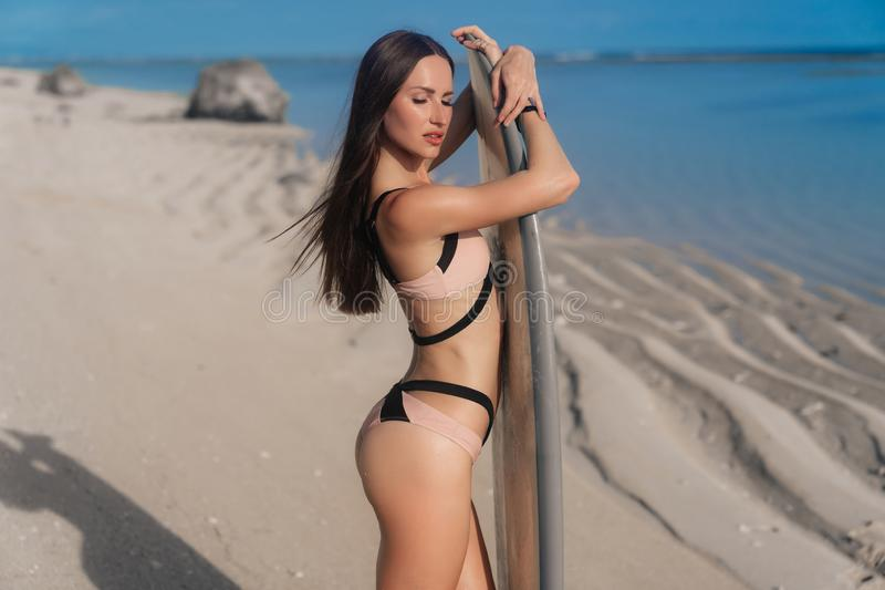 Attractive young woman in swimsuit standing on beach with surfboard stock photo