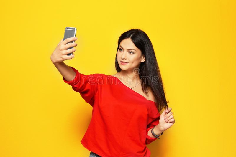 Attractive young woman taking selfie. On color background royalty free stock image