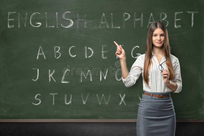 Attractive young woman teacher in a classroom royalty free stock photo
