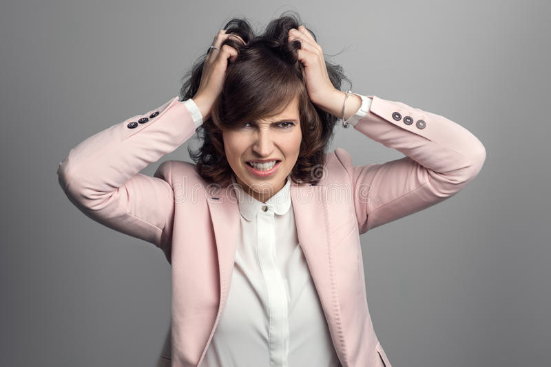 Attractive young woman tearing at her hair royalty free stock photography