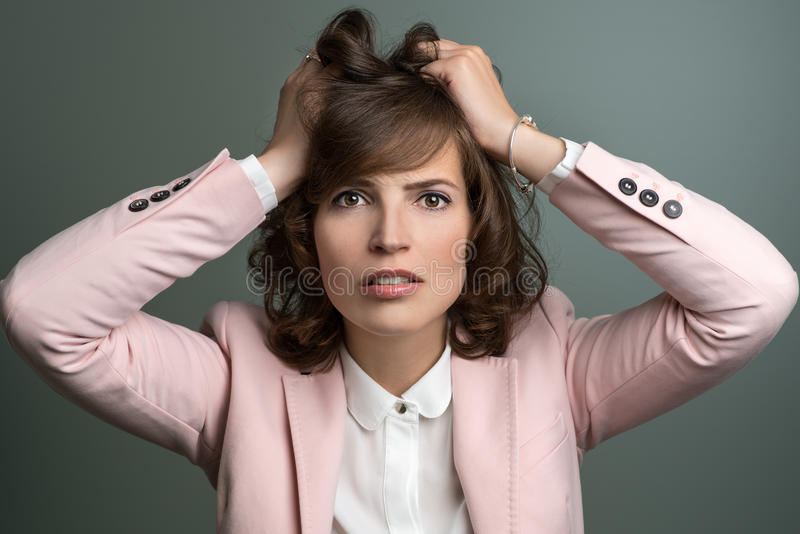 Attractive young woman tearing at her hair royalty free stock image