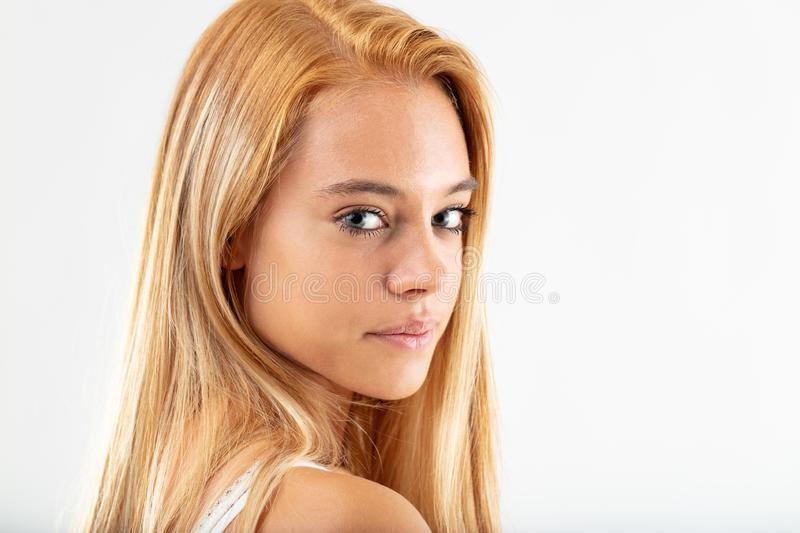 Attractive young woman turning to camera. Attractive young woman turning to look at the camera over her shoulder, with a thoughtful serious expression isolated stock photo