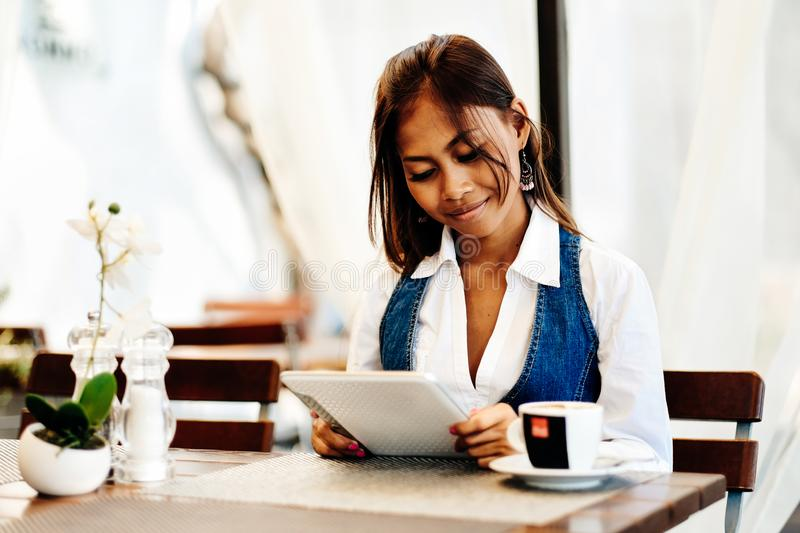 Attractive young woman using digital tablet while drinking coffee in cafe.  royalty free stock photos