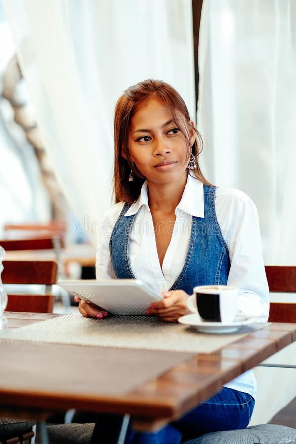 Attractive young woman using digital tablet while drinking coffee in cafe.  stock image
