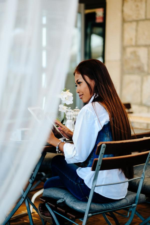Attractive young woman using digital tablet while drinking coffee in cafe.  royalty free stock images