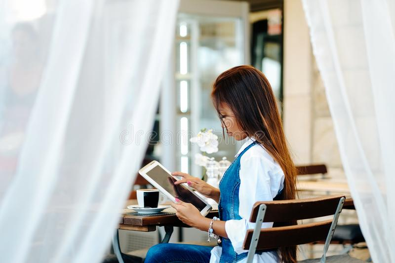 Attractive young woman using digital tablet while drinking coffee in cafe stock images