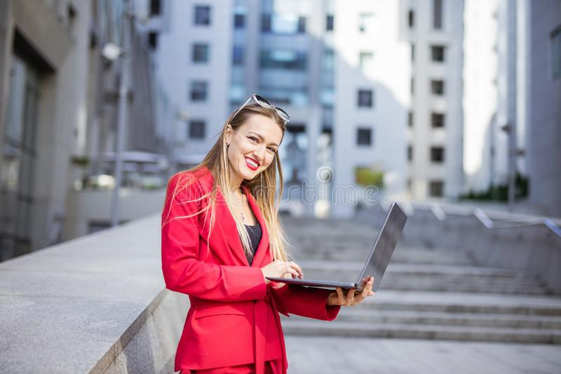 Attractive young woman using laptop in front of office buildings. Attractive young woman using laptop outdoors in front of office buildings royalty free stock image