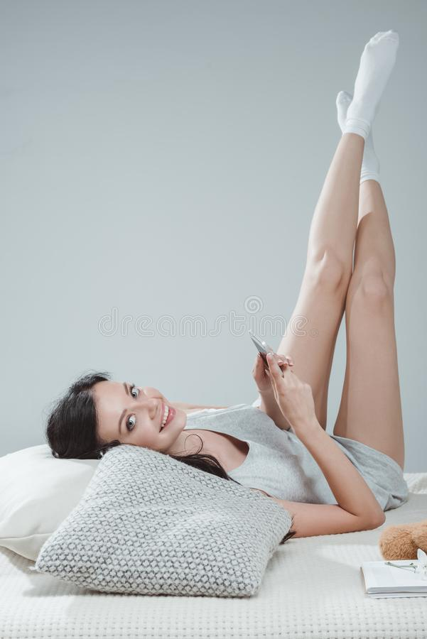 Attractive young woman using smartphone while lying on bed and smiling stock photos