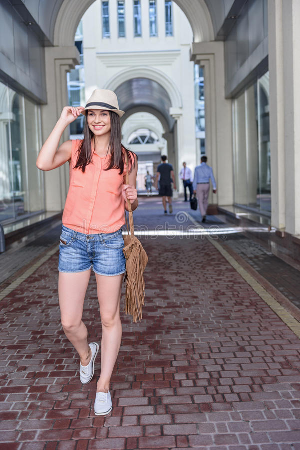 Attractive young woman walking in city. Fashionable girl is enjoying walk in town. She is looking forward with aspiration and smiling. Lady is touching her hat stock image