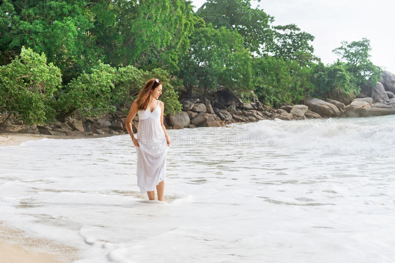 Attractive, young woman walking on the coast and pulling up the dress stock photos