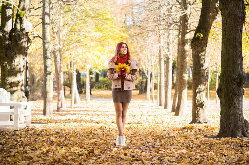 Attractive young woman walking in the park in the autumn time holding colorful foliage royalty free stock photo
