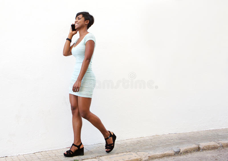Attractive young woman walking on street with cell phone. Full body side portrait of an attractive young woman walking on street with cell phone royalty free stock image