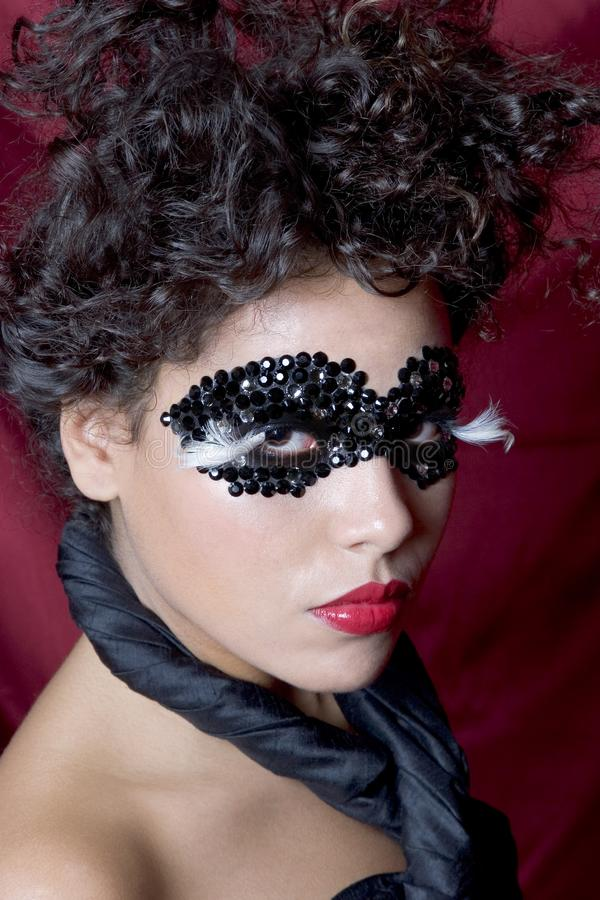 Attractive young woman wearing a black gem mask royalty free stock image