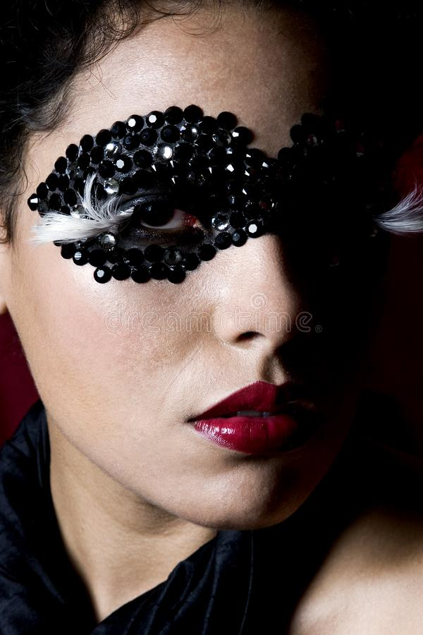 Attractive young woman wearing a black gem mask stock photo