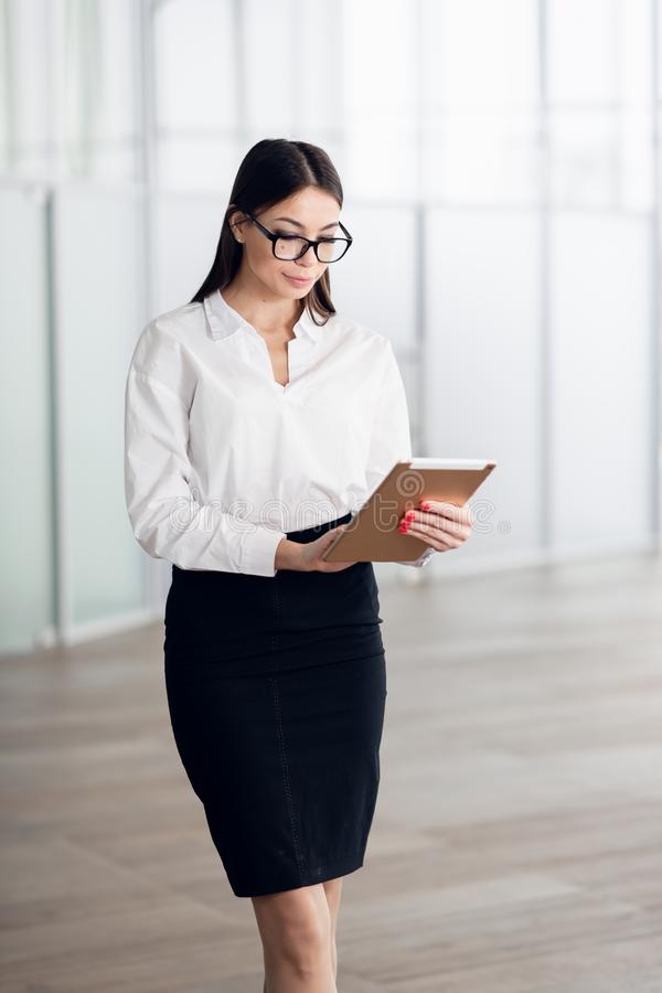 Attractive young woman wearing glasses and reading her touchscreen tablet while standing inside commercial building stock photography