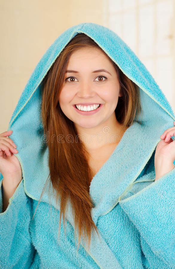 Attractive young woman wearing hooded blue bathrobe royalty free stock photo