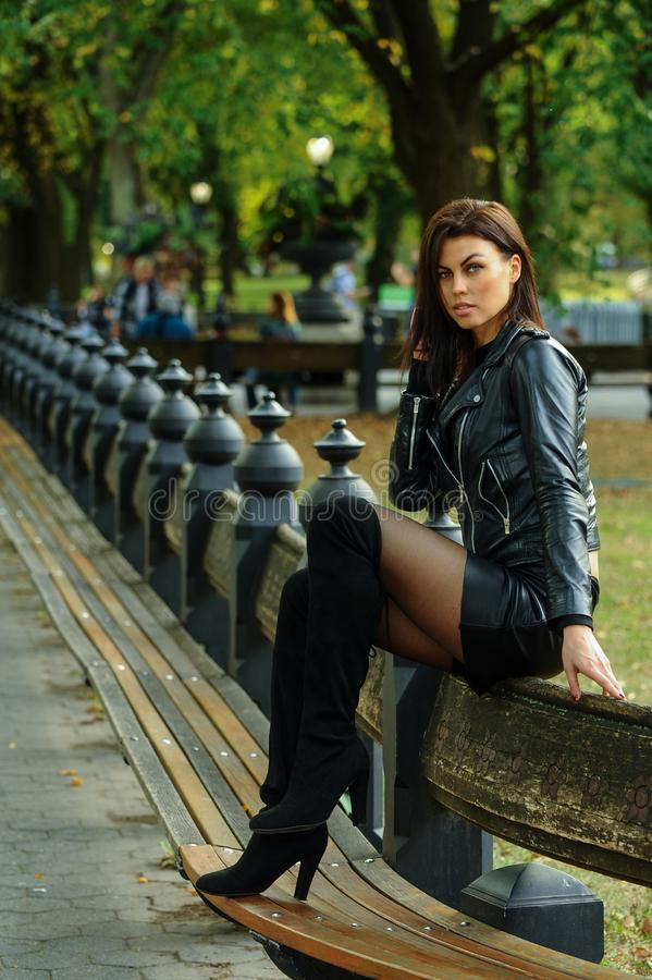 Attractive young woman wearing leather jacket, mini skirt and over-knee boots. Posing at the autumn park royalty free stock photos