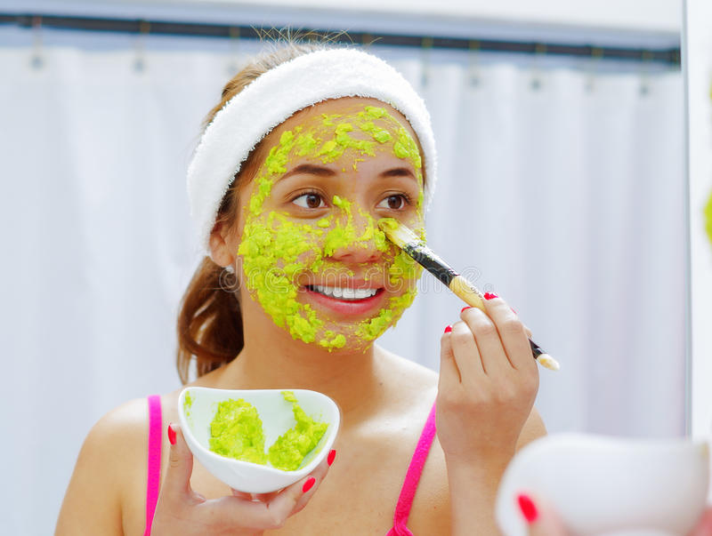 Attractive young woman wearing pink top and white headband, applying avocado mixture to face using brush, looking in stock photo