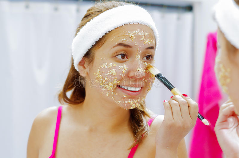 Attractive young woman wearing pink top and white headband, applying oat mixture to face using brush, looking in mirror stock photography
