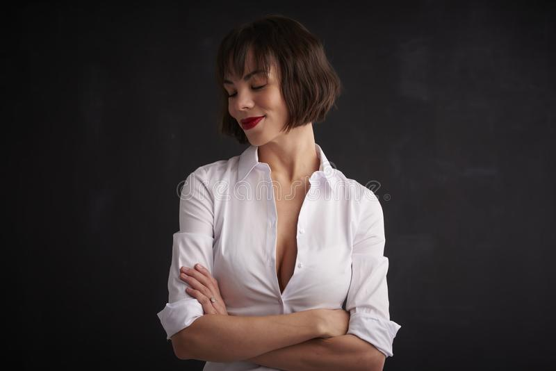 Attractive young woman wearing red lipstick and white shirt while standing at dark bakcground. Portrait shot of beautiful woman wearing red lipstick and white royalty free stock photography
