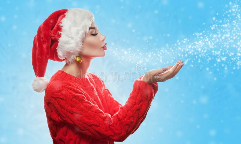 An attractive young woman is wearing a red Santa Claus hat on her head and in a red holiday sweater blows snowflakes and sparkles stock photos