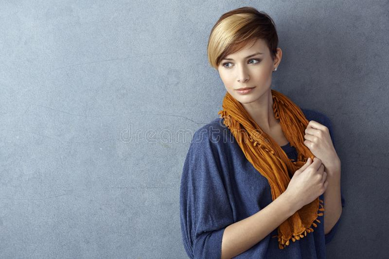 Attractive young woman wearing scarf. Standing by grey wall, looking away. Copy space royalty free stock photo
