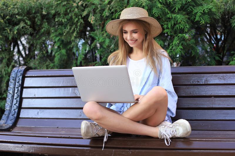 Attractive young woman wearing summer clothes working on laptop while sitting on bench in city street stock photo