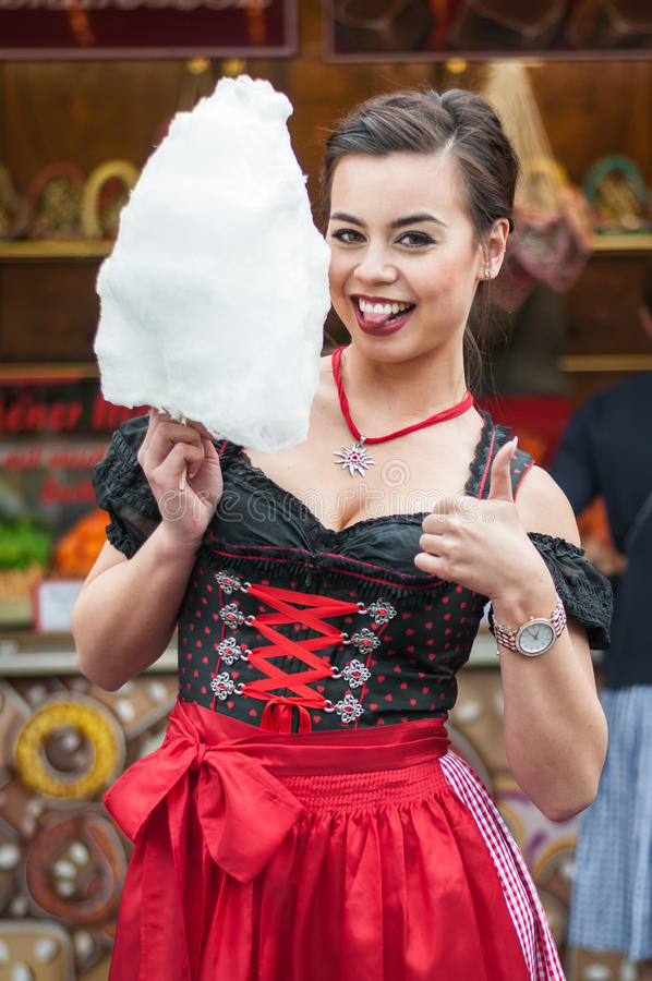 Attractive young woman wearing a traditional Dirndl dress with cotton candy floss at the Oktoberfest. royalty free stock image