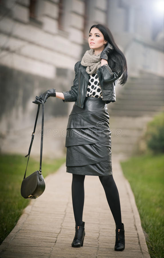 Attractive young woman in a winter fashion shot. Beautiful fashionable young girl in black leather outfit posing on avenue stock photography