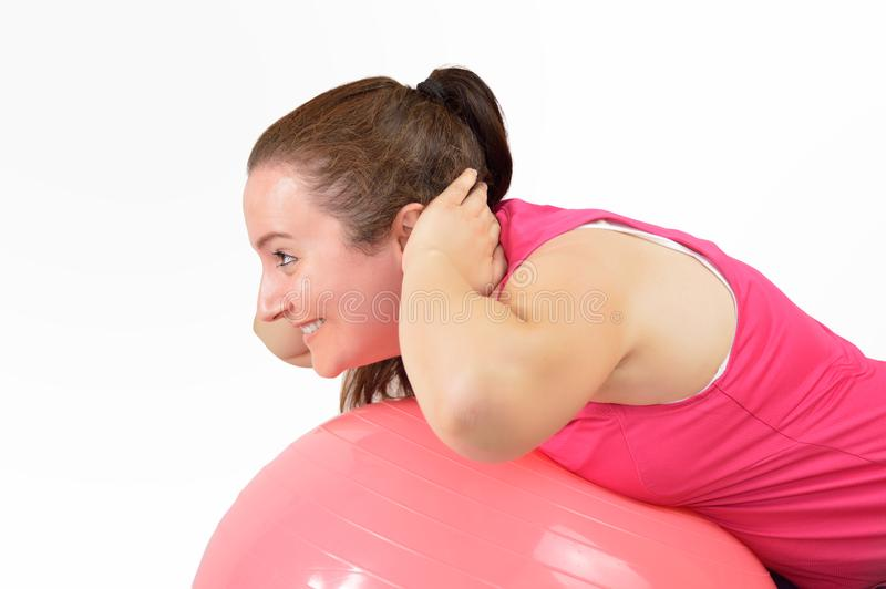 Attractive young woman working out with an exercise bal stock photography