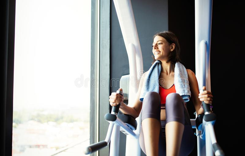 Attractive young woman working out at a gym. royalty free stock photography