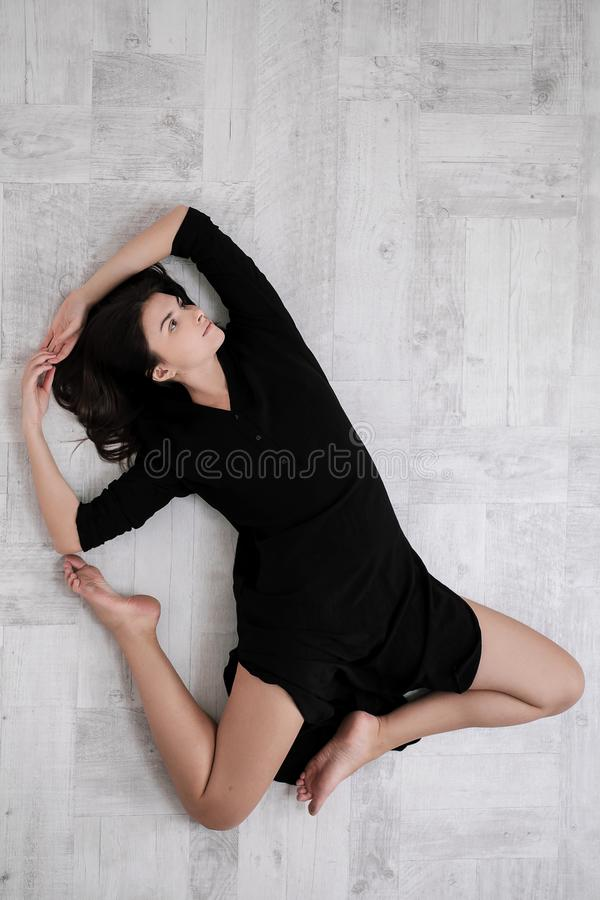 Attractive young woman working out in living room, doing yoga exercise on wooden floor, resting after practice, full stock photo