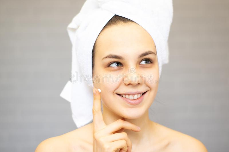 Attractive Young Woman Wrapped with Bath Towels, Applying Cream on her Face After a Shower at the Bathroom stock photo