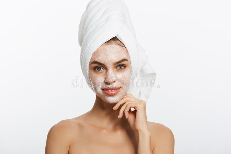 Attractive Young Woman Wrapped with Bath Towels, Applying Cream on her Face After a Shower at the Bathroom. royalty free stock photos