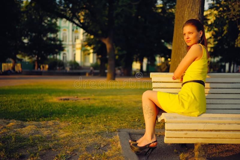 Attractive Young Woman In Yellow Dress, Sitting In A Summer Park On A Bench Stock Photo