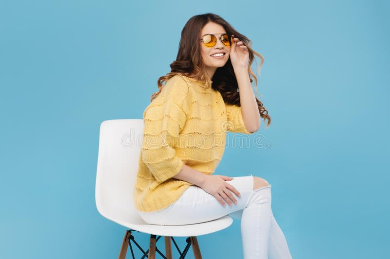 Attractive young woman in yellow sweater posing on blue background. Pretty girl in yellow glasses. Attractive young woman in yellow sweater posing on blue royalty free stock images