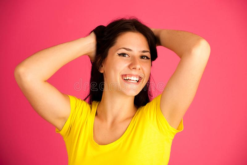 Attractive young woman in yellow t shirt over pink background - royalty free stock photography