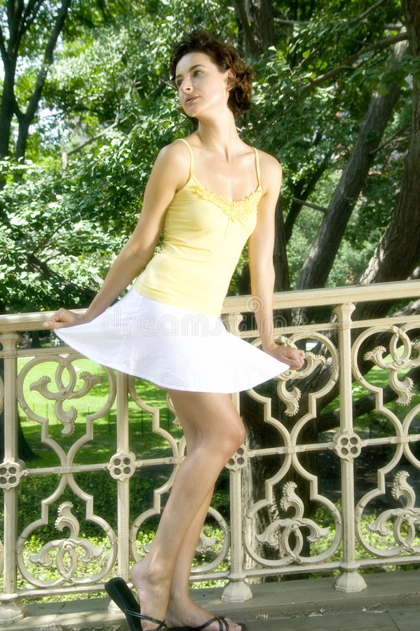 Attractive young woman in yellow vest and white skirt, Central P royalty free stock images