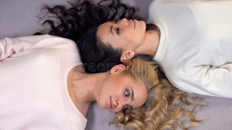 Attractive young women with beautiful long hair lying on floor, photo-shoot stock photos